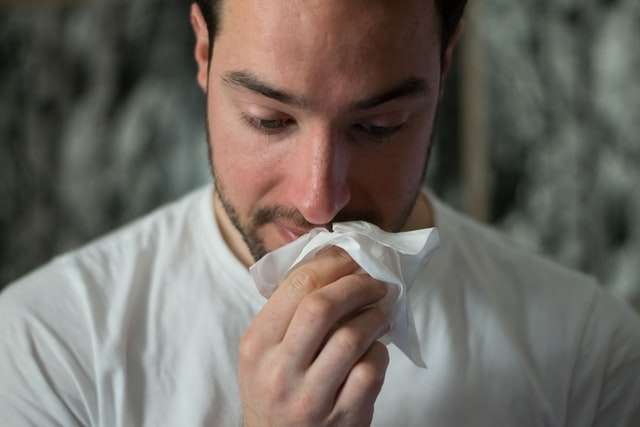 benefits with beards: Man blowing his nose with a tissue.