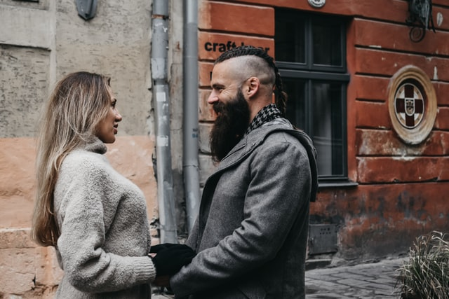 Benefits of beards: Bearded man and lady holding hands and lovingly looking at each other.